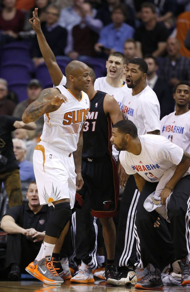 Phoenix Suns' P.J. Tucker, left, celebrates a 3-pointer with teammates on the bench during the first half of an NBA basketball game against the Miami Heat on Tuesday, Feb. 11, 2014, in Phoenix
