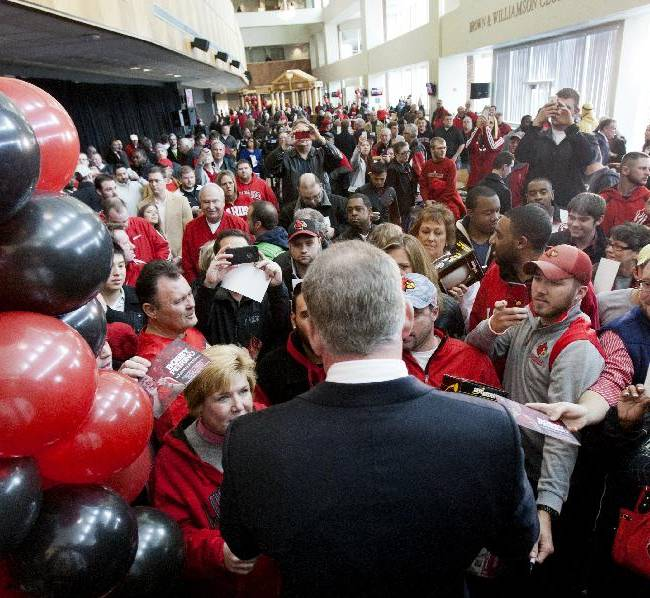 Bobby Petrino signs autographs for fans after being announced as the new University of Louisville football coach at Papa John's Cardinal Stadium, Thursday, Jan. 9, 2014, in Louisville, Ky