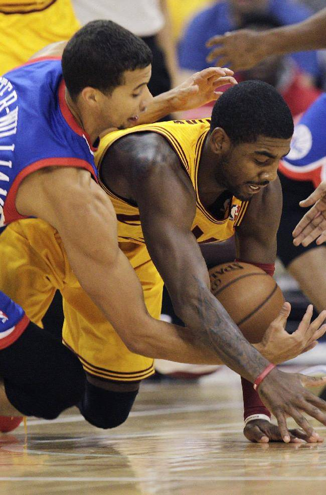 Cleveland Cavaliers' Kyrie Irving, right, and Philadelphia 76ers' Michael Carter-Williams fight for a loose ball during the first quarter of an NBA preseason basketball game Monday, Oct. 21, 2013, in Columbus, Ohio