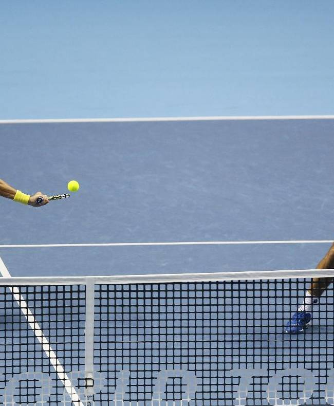 Brazil's Marcelo Melo, left, and Croatia's Ivan Dodig play a returns during their doubles ATP World Tour tennis finals match against France's Julien Benneteau and Edouard Roger-Vasselin at the O2 arena in London, Thursday, Nov. 13, 2014