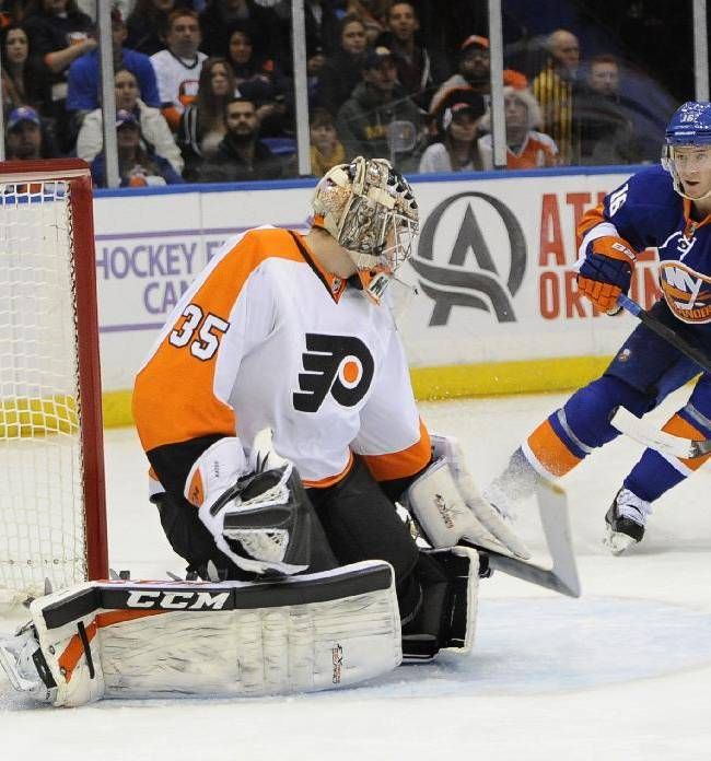 New York Islanders center Peter Regin (16) watches the puck shot by Frans Nielsen fly past Philadelphia Flyers goalie Steve Mason (35) to score in the second period of an NHL hockey game at the Nassau Coliseum on Saturday, Oct. 26, 2013, in Uniondale, N.Y
