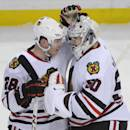 Chicago Black Hawks right winger Ben Smith (28) celebrates with goaltender Corey Crawford (50) after an NHL hockey game against the Buffalo Sabres in Buffalo, N.Y., Sunday, March 9, 2014. Chicago won 2-1. (AP Photo/Gary Wiepert)