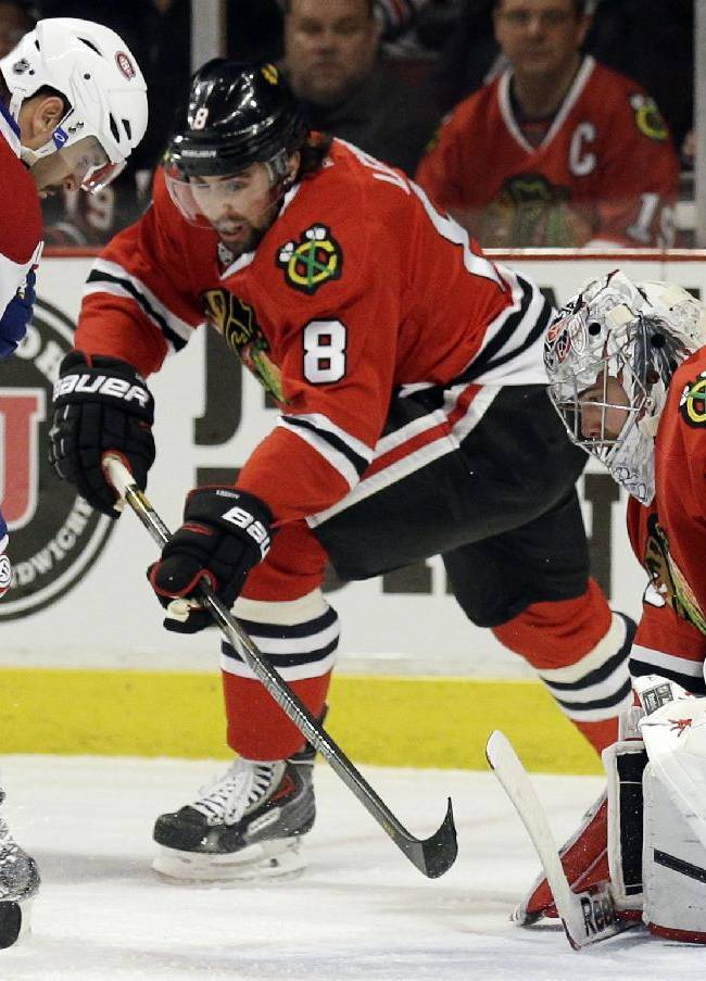 Montreal Canadiens' Brian Gionta (21) shoots against Chicago Blackhawks goalies Corey Crawford (50) during the first period of an NHL hockey game in Chicago, Wednesday, April 9, 2014