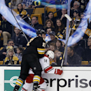 Boston Bruins' Milan Lucic (17) checks Carolina Hurricanes' Nathan Gerbe (14) and bends the glass during the first period of an NHL hockey game in Boston, Saturday, Nov. 15, 2014. The Bruins won 2-1 The Associated Press