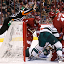 Referee Ian Walsh, left, leaps on the goal as he stops play as Minnesota Wild's Niklas Backstrom (32), of Finland, makes a save as Arizona Coyotes' Martin Hanzal (11), of the Czech Republic, and Tobias Rieder (8), of Germany, wait for the puck to come out