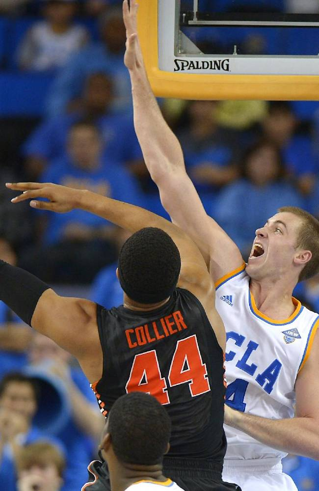 Oregon State forward Devon Collier, left, puts up a shot as UCLA forward Travis Wear defends during the second half of an NCAA college basketball game, Sunday, March 2, 2014, in Los Angeles. UCLA won 74-69
