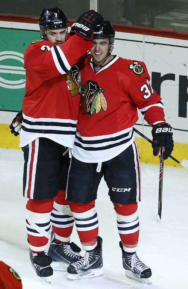 Chicago Blackhawks defenseman Brent Seabrook (7) and center Brandon Pirri (37) celebrate after Pirri scored a goal against the Toronto Maple Leafs during the second period of an NHL hockey game on Saturday, Oct. 19, 2013, in Chicago