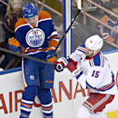 New York Rangers' Tanner Glass (15) checks Edmonton Oilers' Jeff Petry (2) during second period of an NHL hockey game in Edmonton, Alberta, Sunday, Dec, 14, 2014 The Associated Press