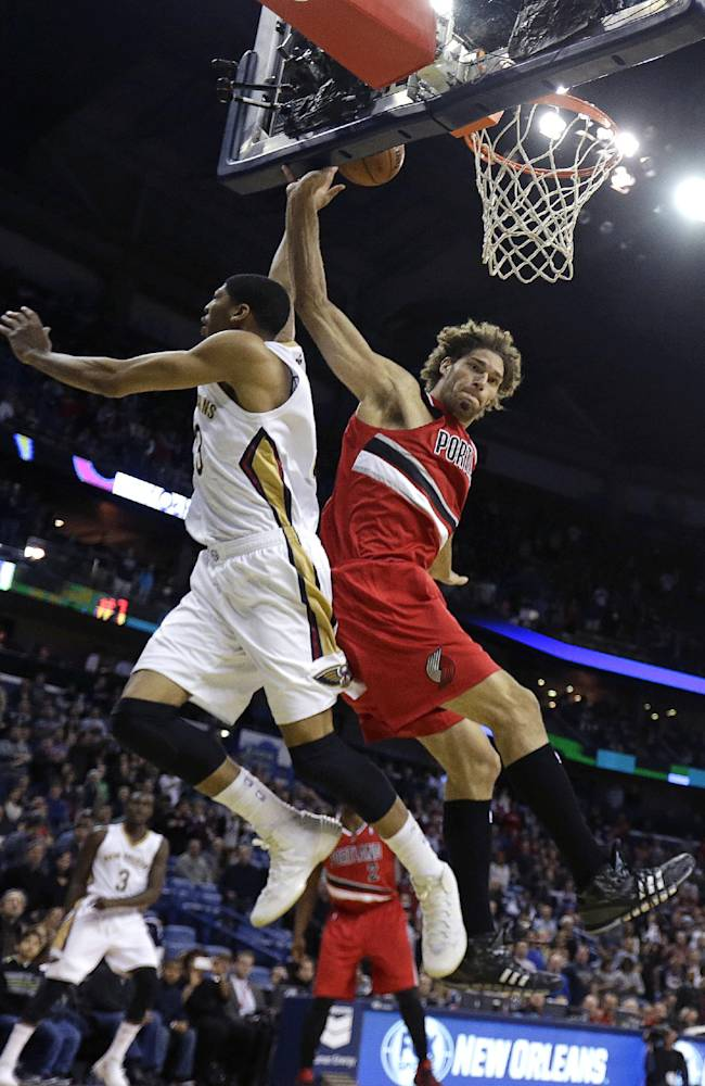 New Orleans Pelicans forward Anthony Davis goes to the basket against Portland Trail Blazers center Robin Lopez, right, in the first half of an NBA basketball game in New Orleans, Monday, Dec. 30, 2013