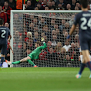 Manchester United's goalkeeper David De Gea, centre left, makes a save, during his team's 3-0 win against Olympiakos in their Champions League last 16 second leg soccer match at Old Trafford Stadium, Manchester, England, Wednesday, March 19, 2014