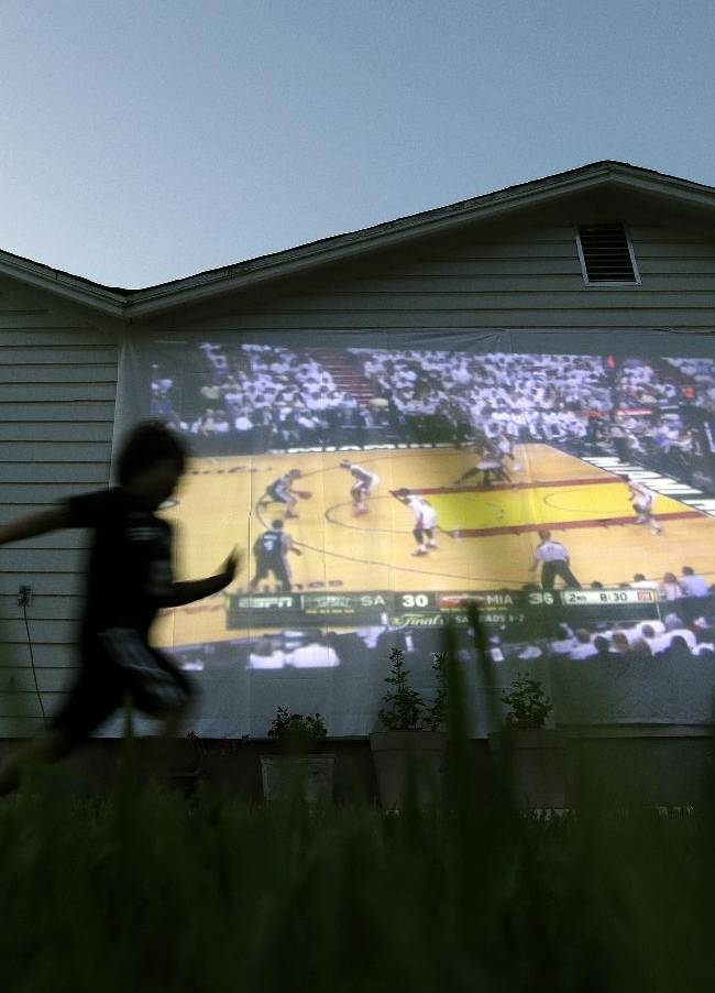 R.J. Cardenas runs past a screen displaying a broadcast of Game 6 in the NBA Finals basketball series between the San Antonio Spurs and the Miami Heat, Tuesday, June 18, 2013, in San Antonio