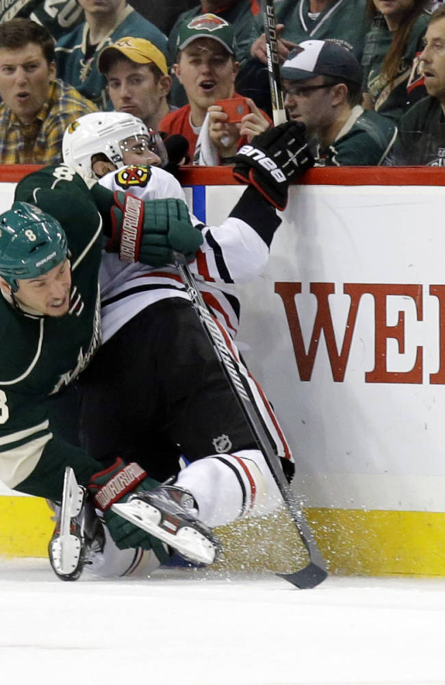 Minnesota Wild center Cody McCormick (8) and Chicago Blackhawks defenseman Nick Leddy, right, tangle as they battle for the puck during the second period of Game 6 of an NHL hockey second-round playoff series in St. Paul, Minn., Tuesday, May 13, 2014. The Blackhawks won 2-1 in overtime