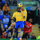 Arsenal s Per Mertesacker, center, clashes heads with teammate Bacary Sagna watched by Cardiif City s Fraizer Campbell, right, during the English Premier League soccer match at Cardiff City Stadium, Cardiff, Wales, Saturday, Nov. 30, 2013