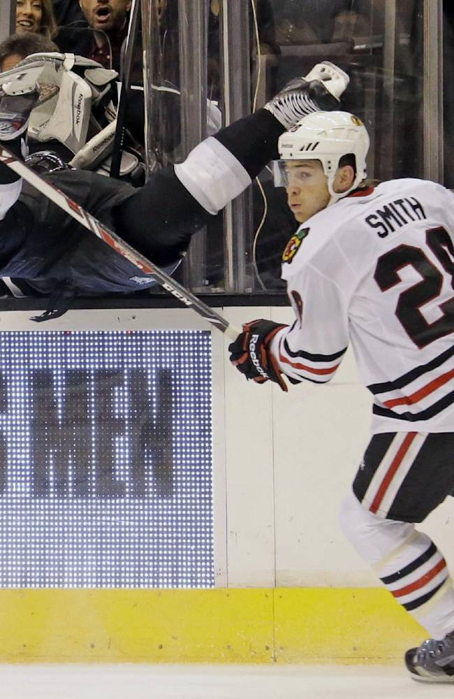 Chicago Blackhawks right winger Ben Smith (28) checks Los Angeles Kings defenseman Jake Muzzin (6) into the Kings bench in the third period of an NHL hockey game in Los Angeles, Monday, Feb. 3, 2014. The Blackhawks won 5-3