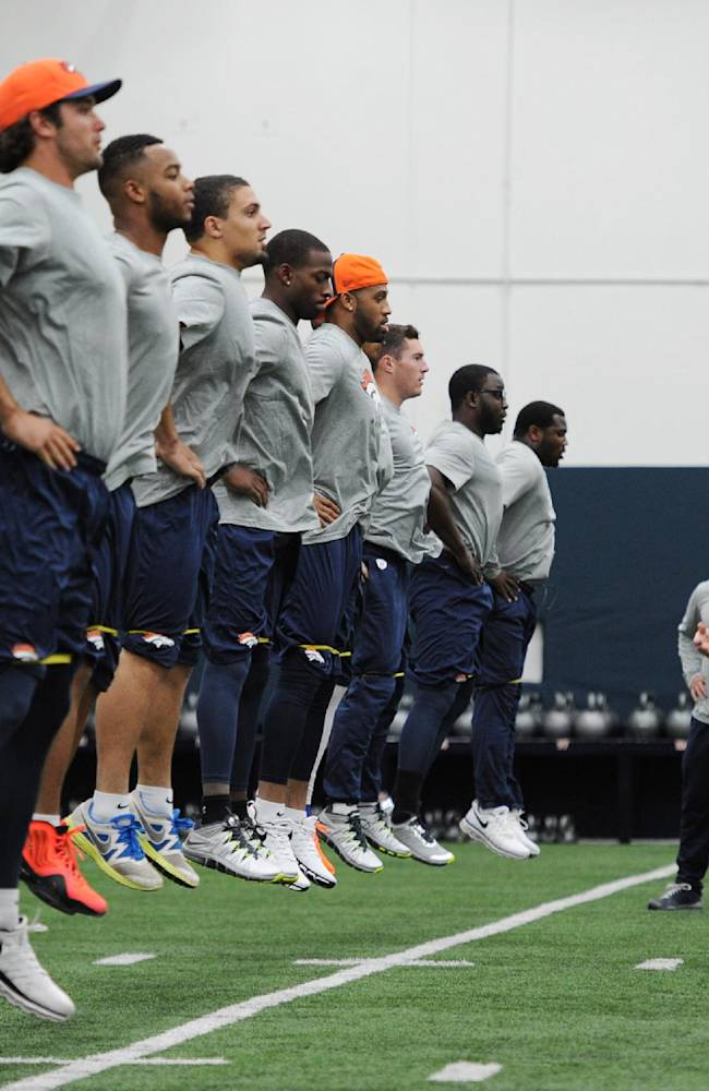 This photo provided by the Denver Broncos shows Strength and Conditioning coach Luke Richesson, right, working with players during an offseason traiing session at the NFL football teams training facility in Englewood, Colo., on Monday, April 21, 2014