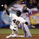 Los Angeles Dodgers second baseman Justin Turner, top, turns a double play over San Francisco Giants' Gregor Blanco after a ground ball by Brandon Hicks during the eighth inning of a baseball game on Tuesday, April 15, 2014, in San Francisco The Associate