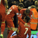Liverpool's Luis Suarez, center, is mobbed by teammates Joe Allen, left, and Glen Johnson after scoring the fourth goal of the game during their English Premier League soccer match against Norwich City at Anfield in Liverpool, England, Wednesday Dec. 4, 2