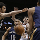 New Orleans Pelicans' Eric Gordon (10) passes the ball against Milwaukee Bucks' ZaZa Pachulia, left, during the second half of an NBA basketball game Wednesday, Feb. 12, 2014, in Milwaukee The Associated Press