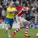 Stoke's Peter Crouch, right, fights for the ball against Newcastle United's Dan Gosling during their English Premier League soccer match at the Britannia Stadium, Stoke, England, Saturday April 12, 2014