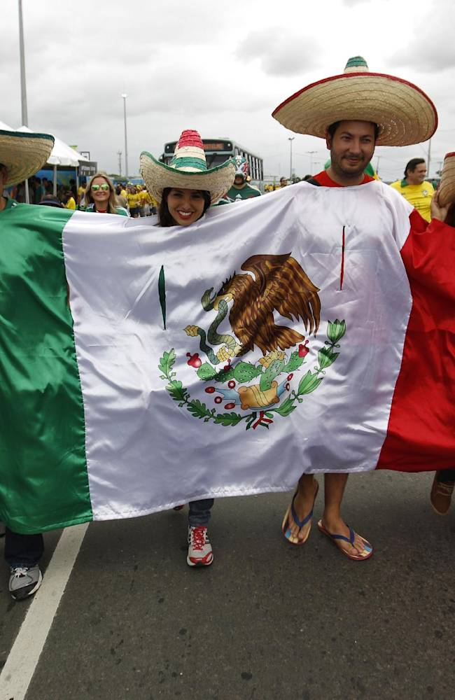 Mexican fans walk to the Arena Castelao draped in their national flag before the group A World Cup soccer match between Brazil and Mexico at the Arena Castelao in Fortaleza, Brazil, Tuesday, June 17, 2014