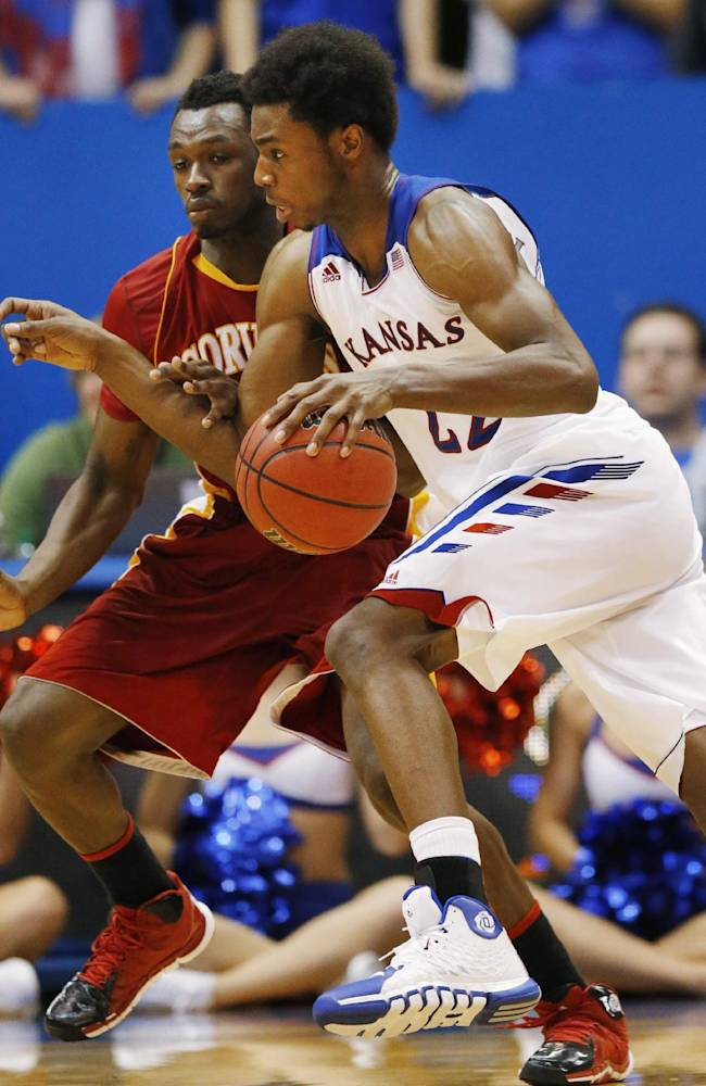 Kansas guard Andrew Wiggins (22) drives on Pittsburg State guard Ethan Cordray, left, during the second half of an exhibition NCAA college basketball game in Lawrence, Kan., Tuesday, Oct. 29, 2013. Kansas won 97-57