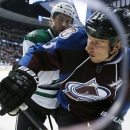 Colorado Avalanche left wing Cody McLeod, front, is checked into the boards by Dallas Stars defenseman Jason Demers in the first period of an NHL hockey game Saturday, Jan. 10, 2015, in Denver The Associated Press