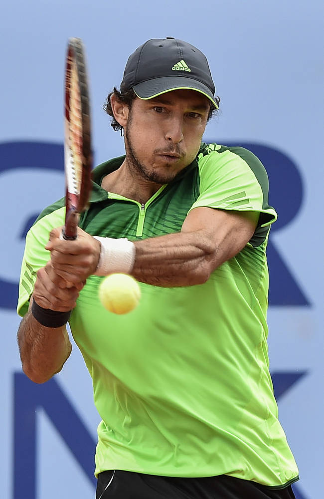 Juan Monaco of Argentina returns a ball to Robin Haase of the Netherlands during the semifinal match at the Swiss Open tennis tournament in Gstaad, Switzerland, Saturday, July 26, 2014