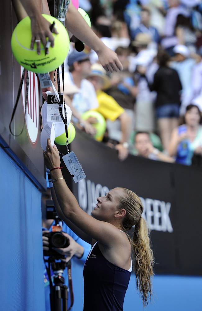 Dominika Cibulkova of Slovakia signs autographs for fans after defeating Agnieszka Radwanska of Poland during their semifinal at the Australian Open tennis championship in Melbourne, Australia, Thursday, Jan. 23, 2014