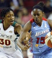 Seattle Storm's Tanisha Wright (30) reaches to try to knock the ball away from Atlanta Dream's Tiffany Hayes during the first half of a WNBA basketball game, Wednesday, July 11, 2012, in Seattle. (AP Photo/Elaine Thompson)