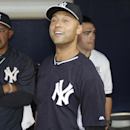 New York Yankees shortstop Derek Jeter, center, and bench coach Tony Pena, left, watch highlights of Jeter's career on a giant video screen in center field during an brief ceremony honoring him for his Turn 2 Foundation prior to a spring exhibition baseb