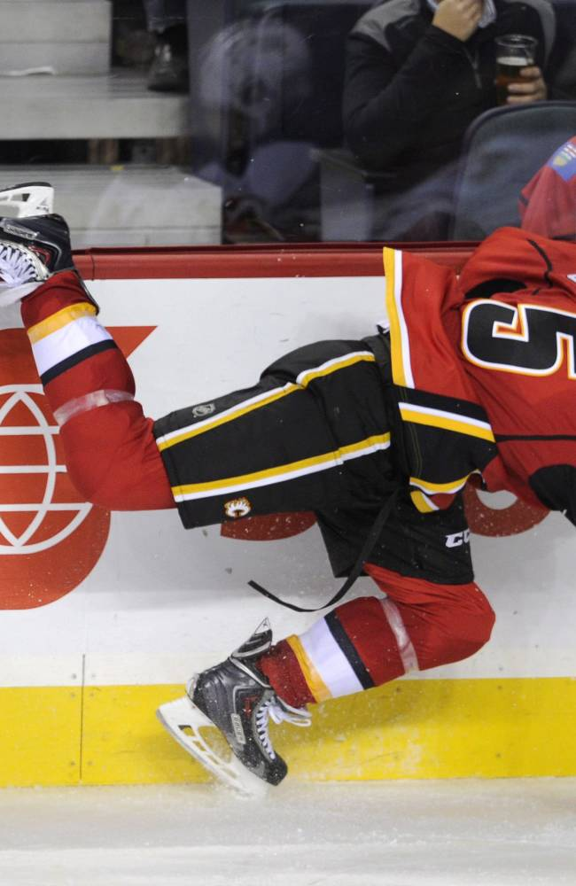Calgary Flames' Mark Giordano, right, is upended along the boards by New Jersey Devils' Dainius Zubrus, from Lithuania, during the third period of an NHL hockey game Friday, Oct. 11, 2013, in Calgary, Alberta. The Flames won 3-2