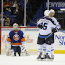 New York Islanders goalie Kevin Poulin (60) reacts as Winnipeg Jets' Devin Setoguchi celebrates his goal with Matt Halischuk (15) in the second period of an NHL hockey game on Wednesday, Nov. 27, 2013, in Uniondale, N.Y The Associated Press