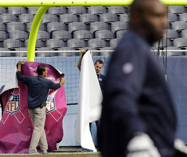 Ground crew covers the goal post with the pink NFL cover for Breast Cancer Awareness month before an NFL football game between the Chicago Bears and the New Orleans Saints, Sunday, Oct. 6, 2013, in Chicago
