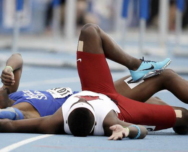 Indiana State's Greggmar Swift, left, collides with Arkansas' Omar McCleod at the finish line of the university men's 110-meter hurdles during the Drake Relays athletics meet, Saturday, April 26, 2014, in Des Moines, Iowa. Swift finished in second place and McLeod third