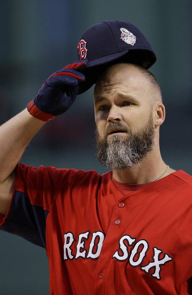 Boston Red Sox's David Ross puts on his cap during practice before Game 1 of baseball's World Series against the St. Louis Cardinals Wednesday, Oct. 23, 2013, in Boston