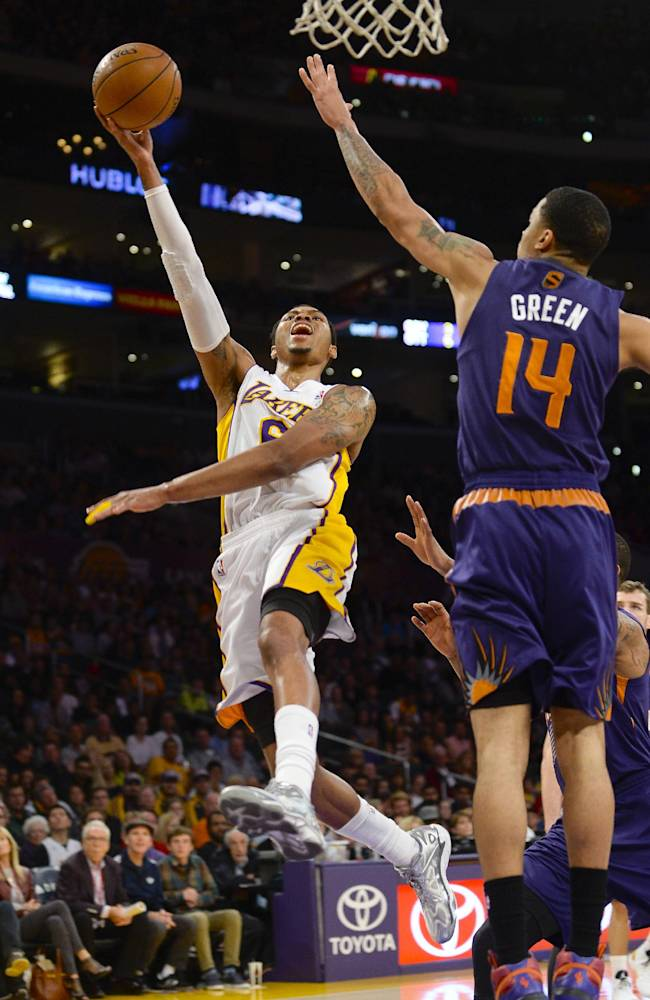 Los Angeles Lakers guard Kent Bazemore (6) drive on Phoenix Suns guard Gerald Green (14) for a basket on a fast break in the first half of an NBA basketball game, Sunday, March 30, 2014, in Los Angeles