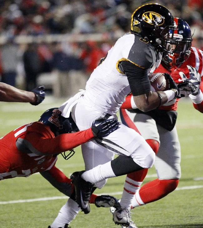 Missouri running back Marcus Murphy, second from right, runs past Mississippi defenders for a three-yard second quarter touchdown run during an NCAA college football game Saturday, Nov. 23, 2013, in Oxford, Miss