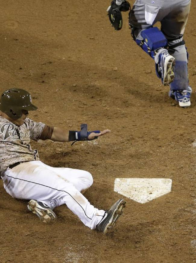 San Diego Padres' Everth Cabrera, left, slides in safely to home, scoring off a two-RBI single by Chris Denorfia against the Los Angeles Dodgers during the eighth inning in an opening night baseball game on Sunday, March 30, 2014, in San Diego