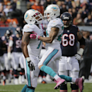 Miami Dolphins defensive end Derrick Shelby (79) celebrates a quarterback sack with cornerback Cortland Finnegan (24) during the first half of an NFL football game against the Chicago Bears Sunday, Oct. 19, 2014 in Chicago The Associated Press