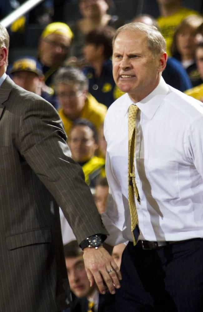 Michigan assistant coach Jeff Meyer, left, holds back head coach John Beilein after Beilein earned a technical foul in the first half of an NCAA college basketball game against Indiana in Ann Arbor, Mich., Saturday, March 8, 2014