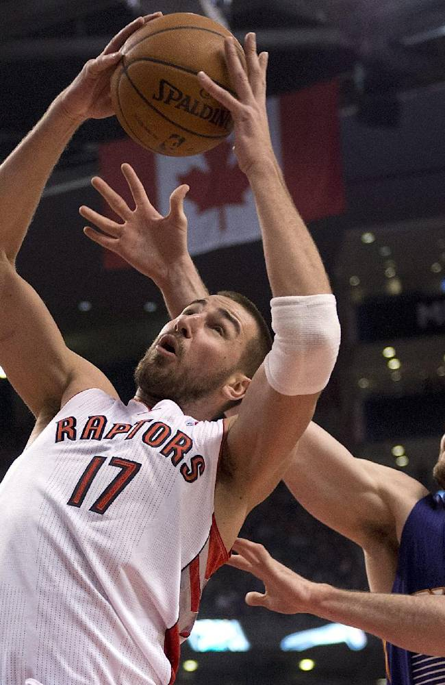 Toronto Raptors center Jonas Valanciunas (17) rebounds against Phoenix Suns center Miles Plumlee (22) during first-half NBA basketball game action in Toronto, Sunday March 16, 2014