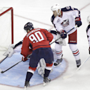 Washington Capitals' Marcus Johansson (90), of sweden, scores a goal on Columbus Blue Jackets goalie Curtis McElhinney as Columbus Blue Jackets' Dalton Prout, center, and James Wisniewski, right, defend during the first period of an NHL hockey game, Tues