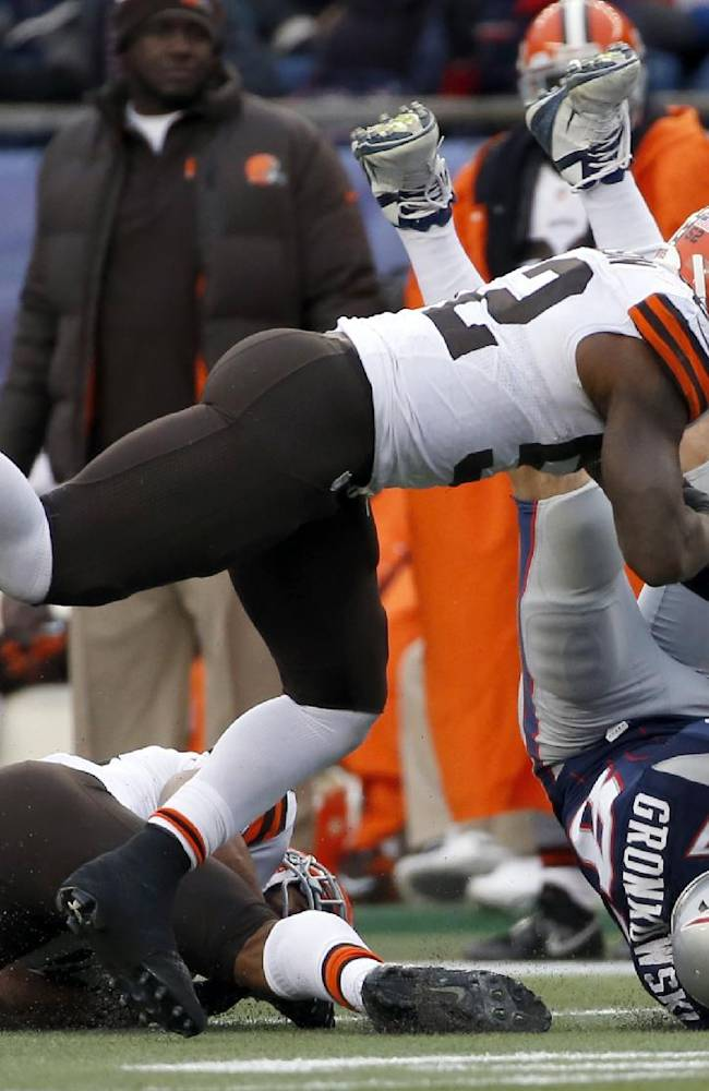 Cleveland Browns safety T.J. Ward, left, and linebacker D'Qwell Jackson, top, tackle New England Patriots tight end Rob Gronkowski (87) after a catch in the third quarter of an NFL football game on Sunday, Dec. 8, 2013, in Foxborough, Mass
