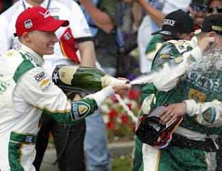 Winner Mike Conway, left, of England sprays his team with champagne in celebration of winning the IndyCar Grand Prix of Long Beach auto race on Sunday, April 13, 2014, in Long Beach, Calif. (AP Photo/Alex Gallardo)
