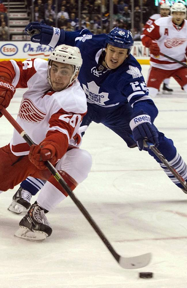 Detroit Red Wings Tomas Jurco, left, battles for the puck with Toronto Maple Leafs' Jerred Smithson during first period NHL hockey action in Toronto on Saturday, Dec 21, 2013