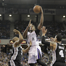 Sacramento Kings forward Rudy Gay, center, drives to the basket between San Antonio Spurs' Boris Diaw, left, of France and Danny Green during the third quarter of an NBA basketball game in Sacramento, Calif., Friday, March 21, 2014. The Spurs won 99-79 T