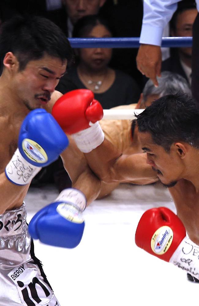 Thailand's Denkaosen Kaovichit, right, and Japan's Kohei Kono exchange punches in the second round of their boxing match for the vacant WBA World super flyweight title in Tokyo, Wednesday, March 26, 2014. Kono knocked out Denkaosen in the eighth round to clinch the title