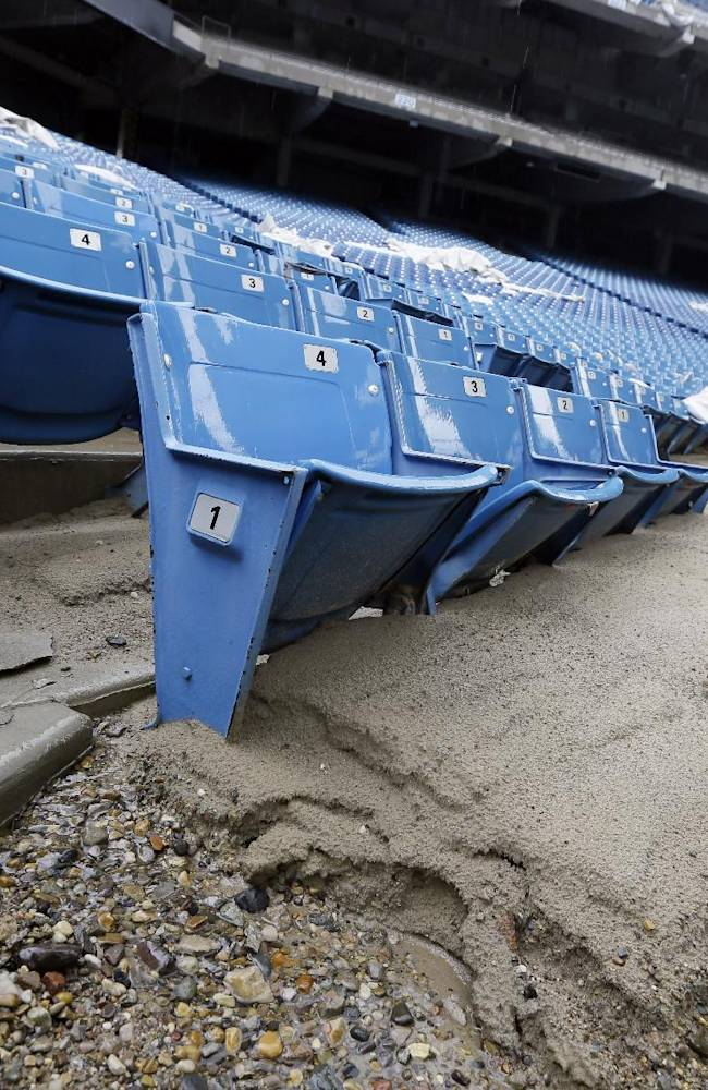 In this May 12, 2014 photo, foundation sand from cracked cement covers seats inside the Pontiac Silverdome in Pontiac, Mich. The 80,000-seat indoor stadium hosted the Super Bowl, the NBA finals, the World Cup, Wrestlemania and concerts by Elvis Presley, Led Zeppelin and the Rolling Stones. Nowadays, the venue is a shell of its former self with its roof in tatters and a lack of electrical power that has left the stadium's innards dark and mold-covered. The Silverdome's current owner is determined to cash in before it's too late, putting everything inside up for auction starting on Wednesday, May 21