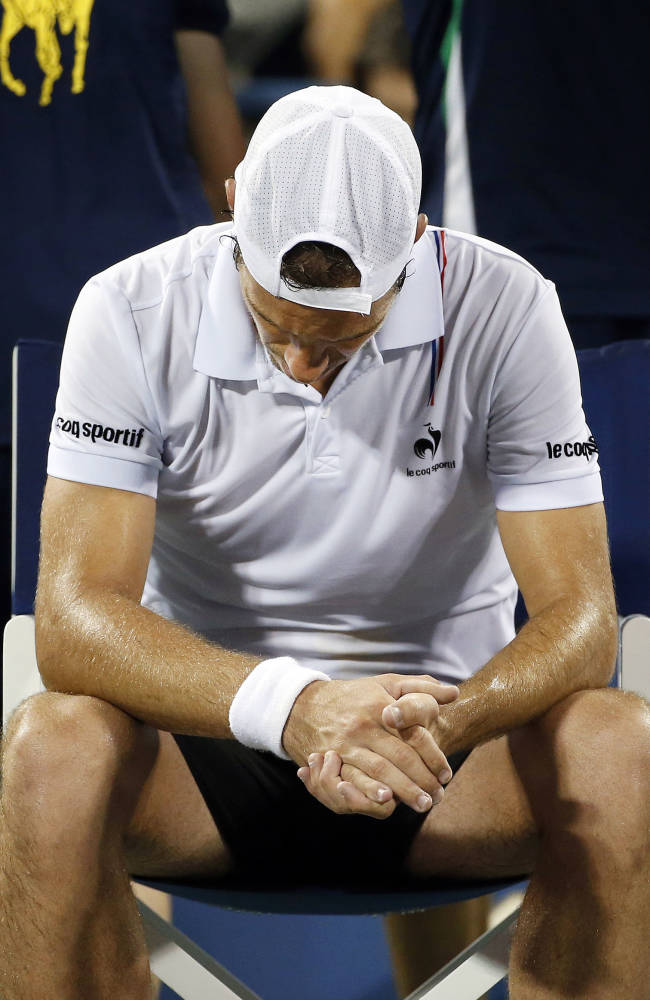 Richard Gasquet, of France, bows his head in a break between games against Gael Monfils, of France, during the third round of the U.S. Open tennis tournament Sunday, Aug. 31, 2014, in New York