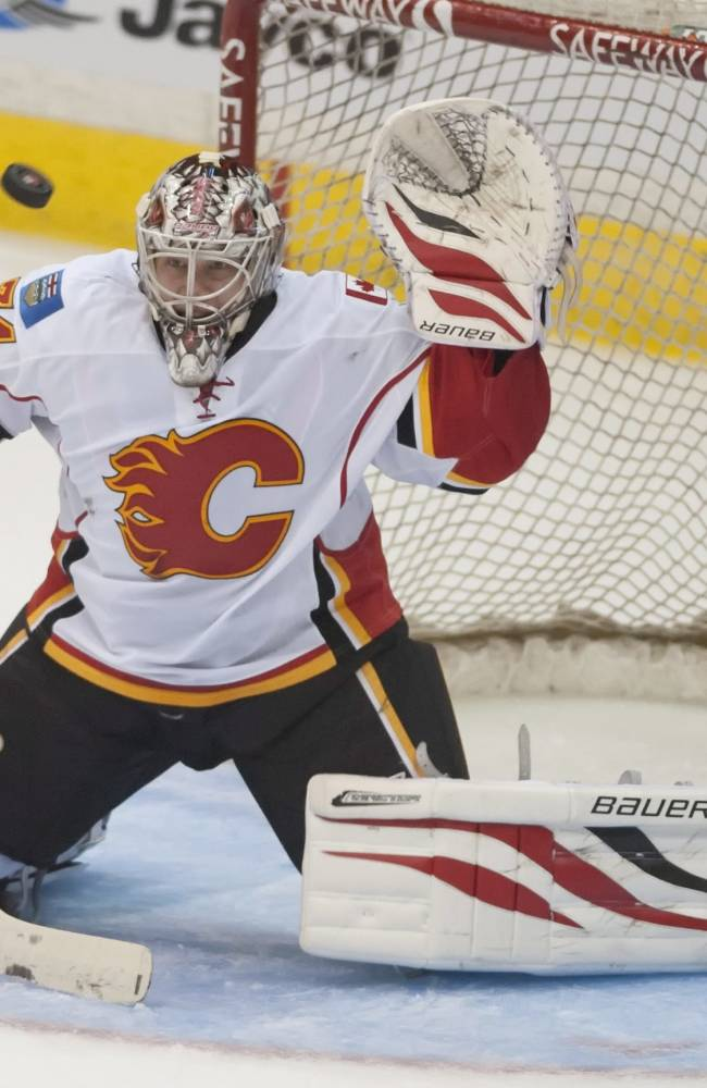 A shot from the New York Islanders goes over Calgary Flames goalie Karri Ramo and the net during the second period of an NHL hockey game Tuesday, Sept. 17, 2013, in Regina, Saskatchewan